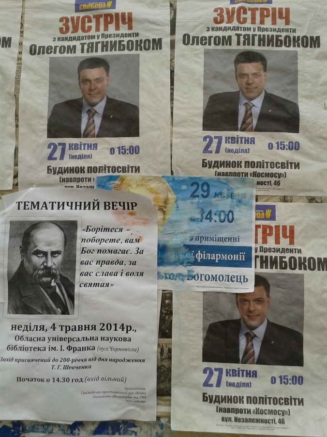 Tyahnybok's poster with Bohomolets' obscured and sodden by rain, with another announcing another Taras Shevchenko-related event