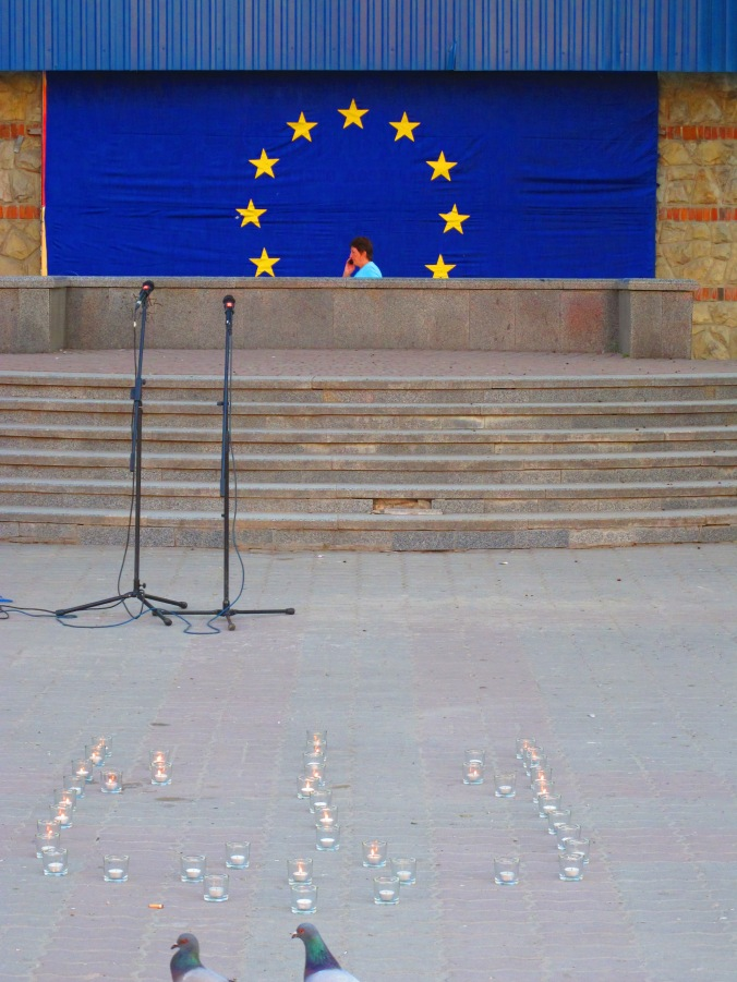 A Ukrainian trident formed of tea-light candles for World Inner Peace Day in front of the EU flag adorning the post office by Rally Square, Ivano-Frankivsk. 26 May 2014. Pro-European Poroshenko won the next day's election.