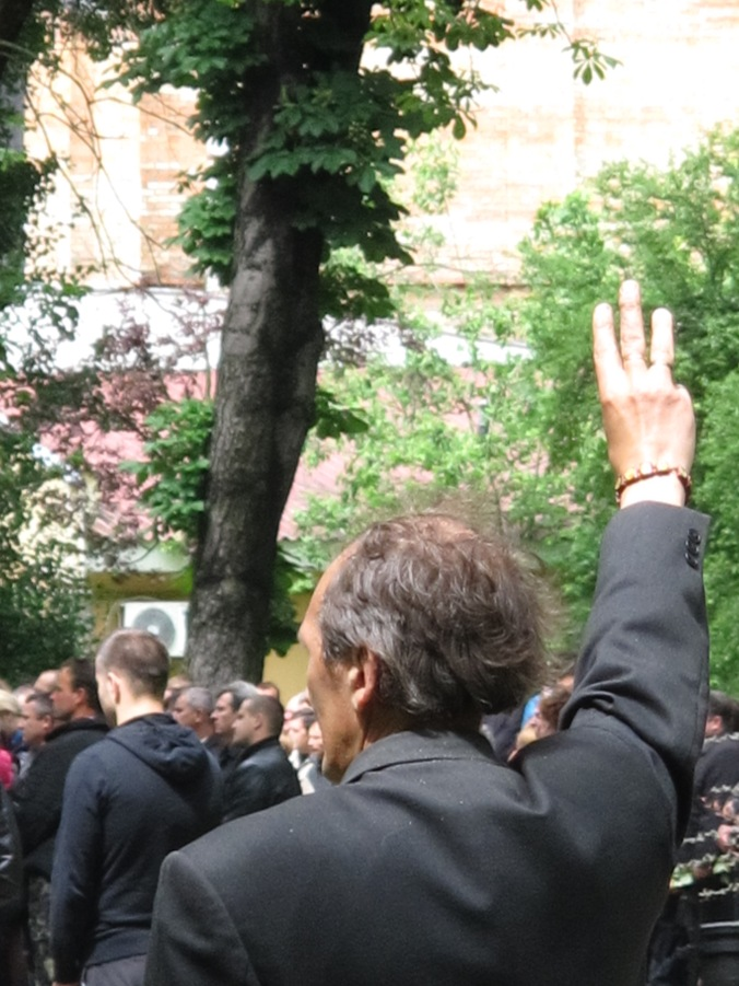 A man gives the Trzyub/Trident salute as the national anthem sounds during the funeral of three Frankivsk men killed near Slovyansk.